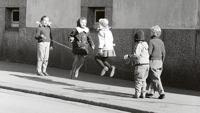 Lapset hyppivät narua jalkakäytävällä. Kuva on otettu 1950–60-lukujen taitteessa.