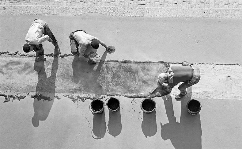 Työmiehet levittävät asvalttia tielle kuumana kesäpäivänä Helsingissä vuonna 1957.
