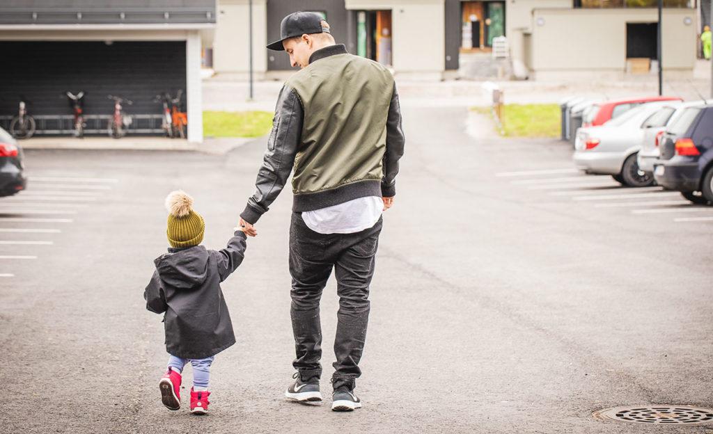 Isä ja pieni lapsi kävelevät käsi kädessä parkkipaikalla