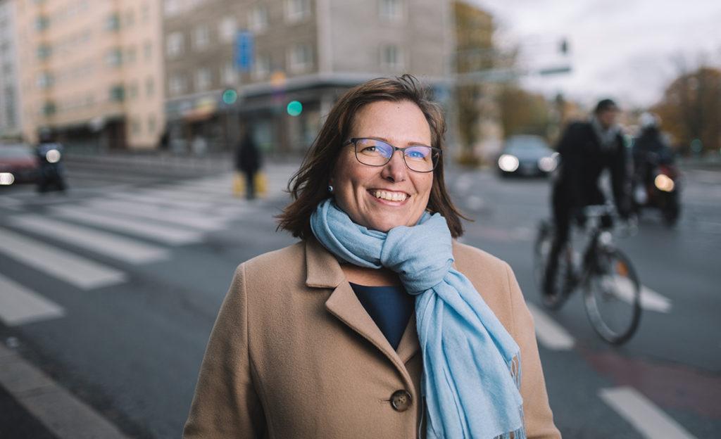 Nina Nissilä seisoo hymyillen Kelan päätalon edustalla Mannerheimintiellä.