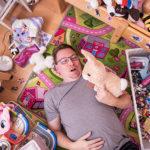 Etäisä Tomi Laaksonen makaa lastenhuoneen lattialla lelujen keskellä ja sylissään pehmolelu