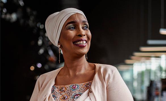 Kuvassa Farhia Abdi hymyilee ja katsoo sivulle