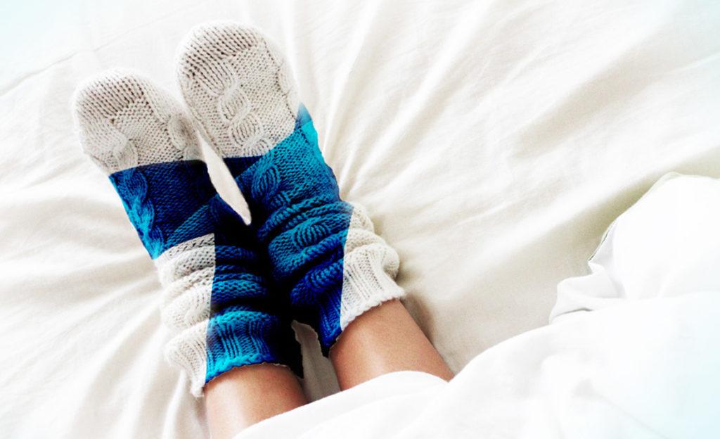 Sängyn peiton alta näkyy jalat, joissa on Suomen lipun kuvioiset villasukat