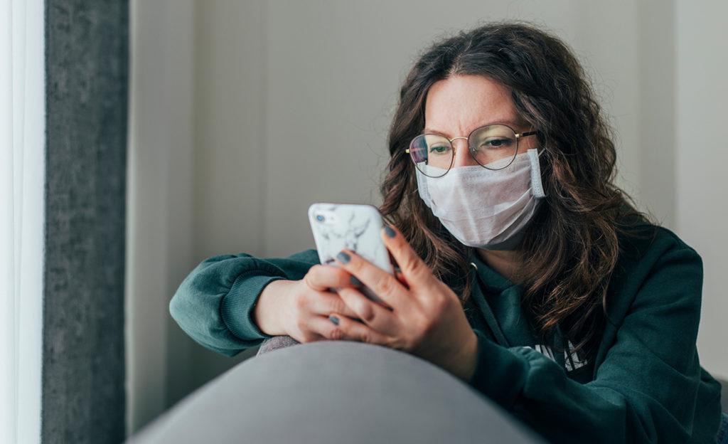 Kuvassa noin parikymppinen henkilä selaa puhelinta maski kasvoillaan.