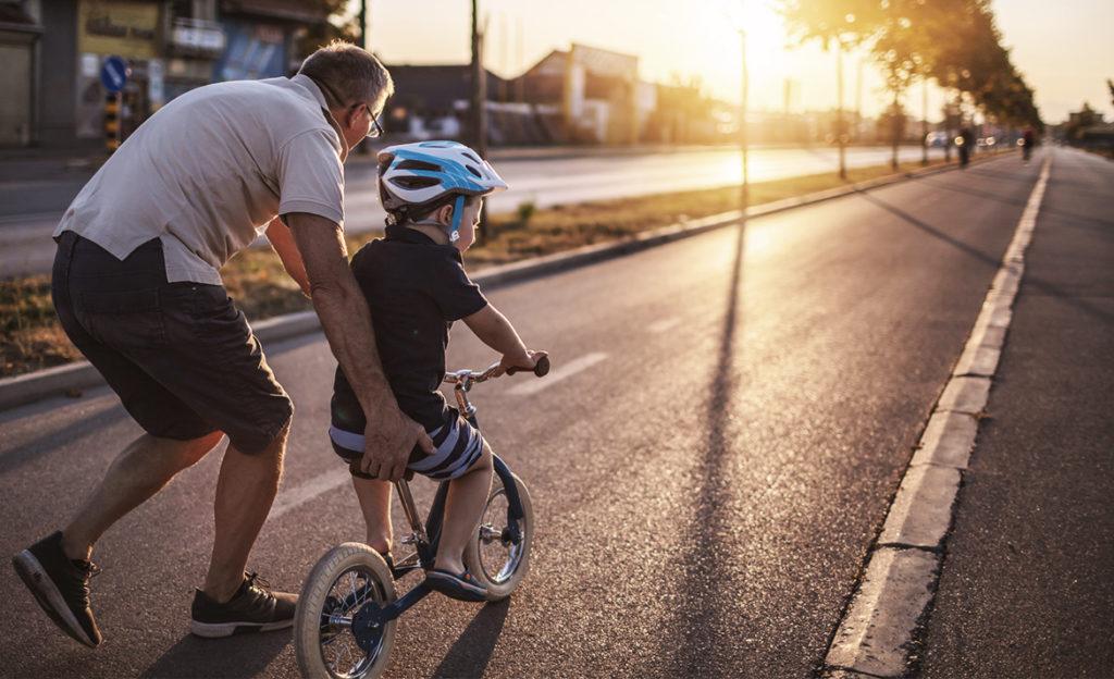 Kuvassa vanhempi henkilö auttaa pientä lasta ajamaan polkupyörällä. Molemmat ovat selin ja suuntaavaat ilta-aurinkoon päin.