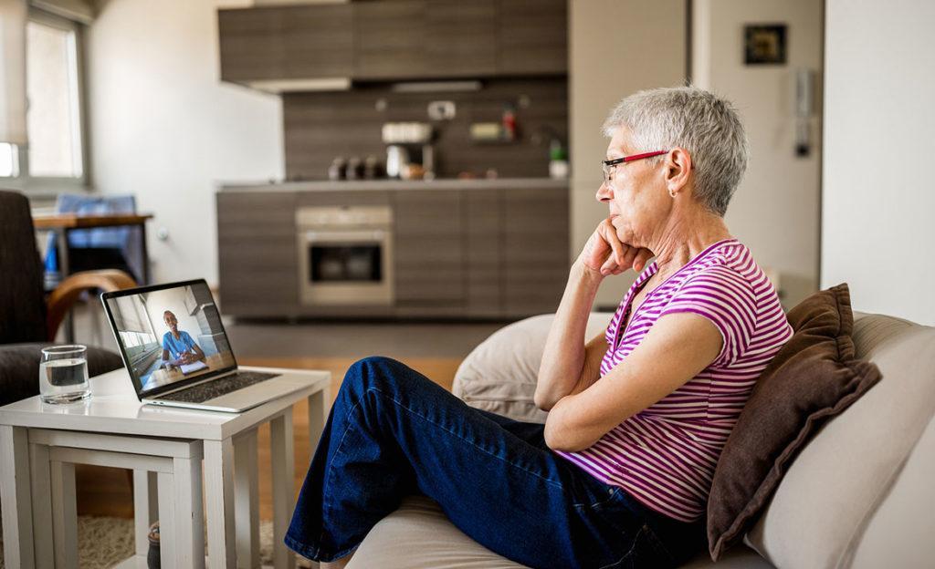 Iäkäs nainen istuu sohvalla ja seuraa tietokoneen ruudulta kun toinen henkilö puhuu hänelle.